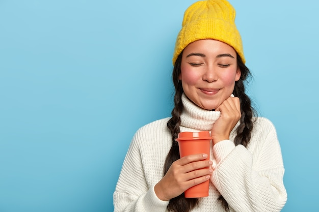 Studio shot of pleasant looking asian woman has two plaits, wears yellow hat and white oversized sweater, holds takeaway coffee, poses against blue background, copy space for your advertising