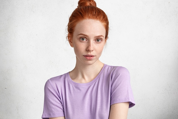 Studio shot of pleasant looking ginger woman with confident look, dressed casually, has pure freckled skin, has attractive look.