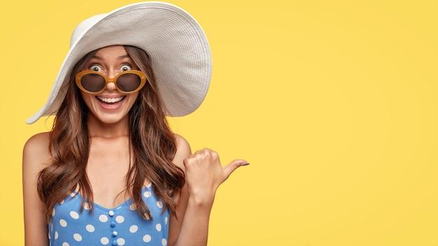 Lo studio ha sparato di giovane signora splendida dall'aspetto piacevole in cappello bianco alla moda, mostra uno spazio vuoto o una direzione