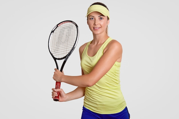 Studio shot of pleasant looking sporty determined female wears court cap