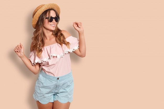 Studio shot of pleased adorable female in summer clothing