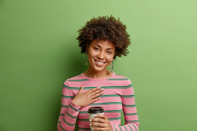 Studio shot of pleased thankful woman keeps hand on chest hears heartwarming words holds disposable cup of coffee tilts head wears striped jumper isolated over vivid green wall