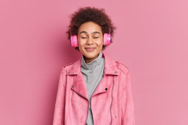Studio shot di lieta giovane donna afroamericana gode di piacevole melodia tiene gli occhi chiusi ascolta musica tramite le cuffie