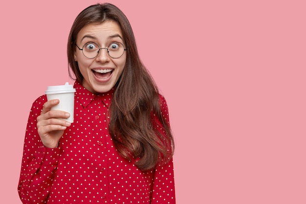 Studio shot of pleased young woman laughs positively, drinks takeaway coffee, has break after lectures
