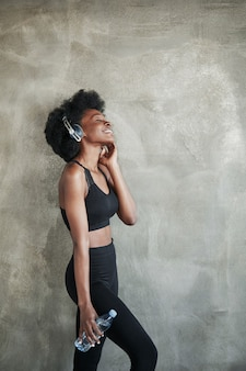 Studio shot. portrait of african american girl in fitness clothes having a break after workout