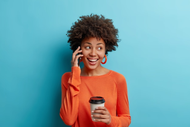 Studio shot of positive afro american woman grabs coffee to go smiles joyfully has telephone talk wears earrings and jumper isolated over blue wall