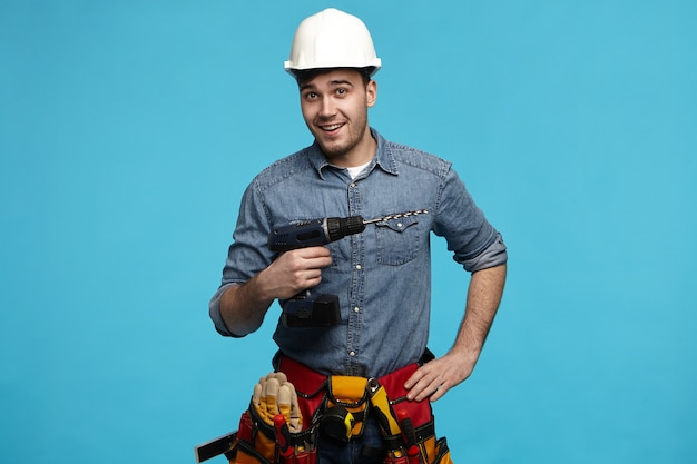 Studio shot of positive friendly young constructor carrying drill and belt with all instruments doing renovation for client