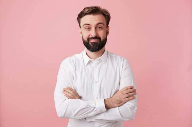 Studio shot of positive young brunette man with beard wearing trendy hairstyle while looking at front with light smile, wearing formal clothes while posing over pink wall