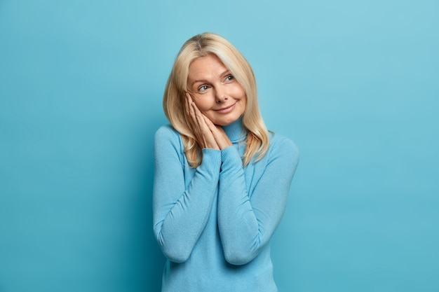 Studio shot of pretty wrinkled middle aged woman keeps hands near face looks thoughtfully aside has dreamy expression