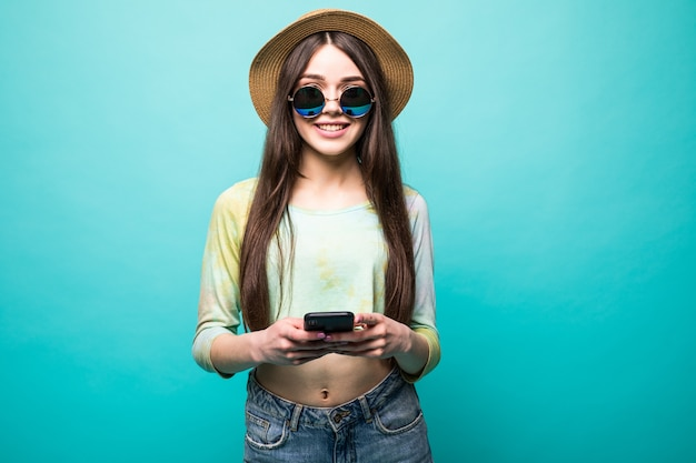 Studio shot di piuttosto giovane ridere donna europea, mostrando il sorriso perfetto del dente, digitando un messaggio al mio ragazzo sul telefono cellulare, tenendo il gadget con una mano isolata su verde