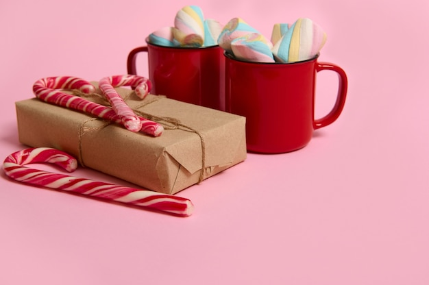 Studio shot of red mugs with colorful marshmallows, christmas gift in craft wrapping paper and striped candy canes on pink colored background. christmas and new year concept with copy space for ad