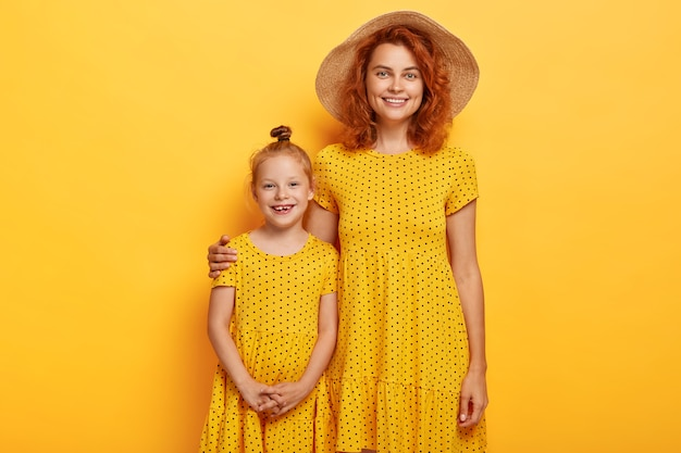 Studio shot of redhead mother and daughter posing in similar dresses