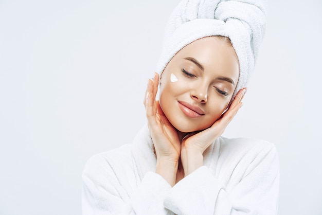 Studio shot of relaxed beautiful woman with closed eyes tilts head, touches skin gently, applies face cream, wears bath towel on head after taking spa procedures, enjoys facial treatments, body care
