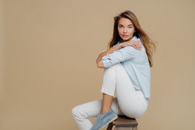 Studio shot of restful beautiful caucasian woman sits on chair, wears shirt, white trousers and shoes