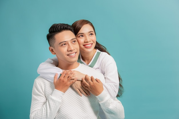 Studio shot of romantic couple posing with smile. front view of girl and boy hugs on blue.