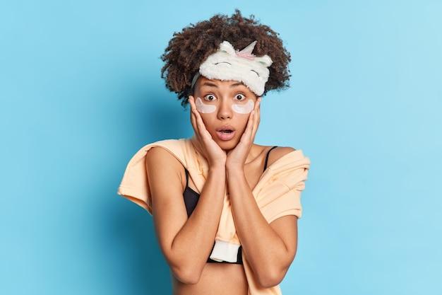 Studio shot di spaventata giovane donna afferra il viso guarda sorprendentemente la fotocamera dopo aver visto incubo indossa blidfold pigiameria applica patch di collagene per ridurre rughe e gonfiori