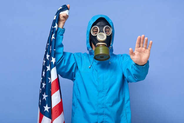 Studio shot of scientist wearing respirator, showing stop gesture with his palm