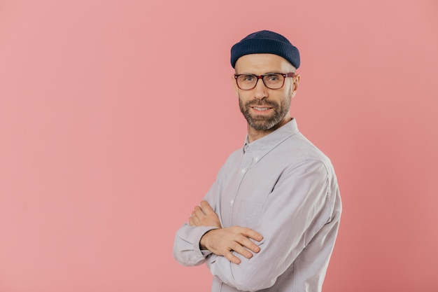 Studio shot of self assured bearded man with blue eyes, wears stylish hat and white shirt, keeps arms folded