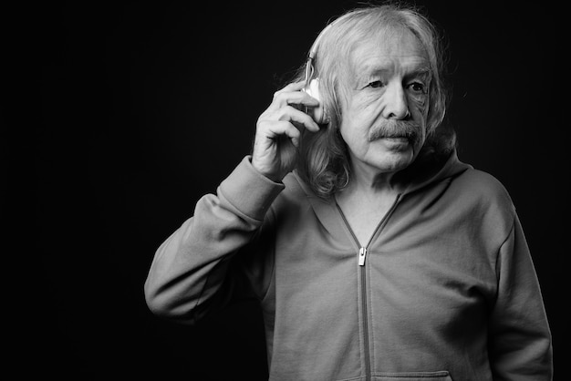 Studio shot of senior man with mustache listening to music against gray wall