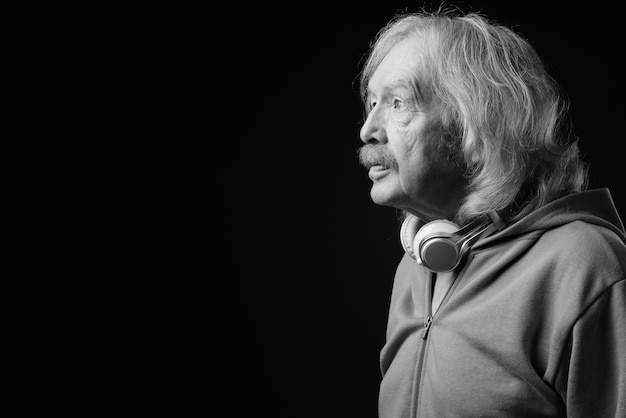 Studio shot of senior man with mustache wearing blue jacket against gray wall