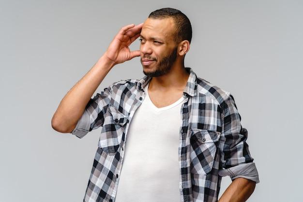 Studio shot of a serious african-american manwearin casual wear with headache.