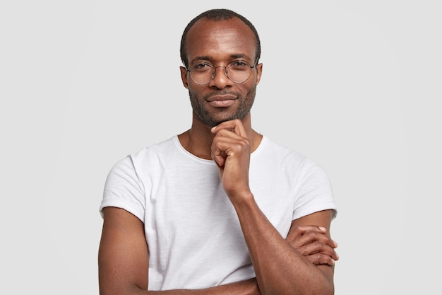 Studio shot of serious black man keeps hand under chin