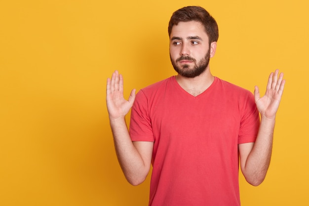 Studio shot of serious casual man keeps hands up isolated over yellow