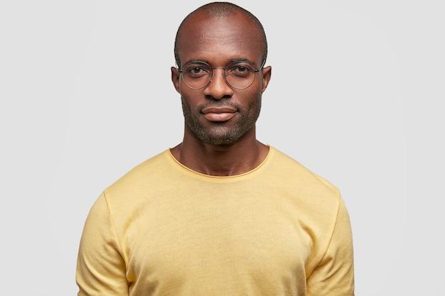 Studio shot di serio fiducioso maschio afroamericano in occhiali