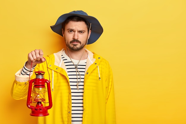 Studio shot of serious discontent man has little beard and mustache, ready for discovering new place in darkness, holds kerosene lamp, dressed in raincoat and heagear.