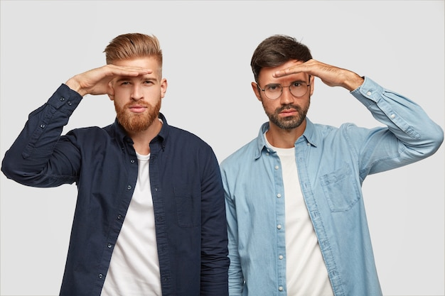 Studio shot of serious guys keep hands near forehead, look seriously into distance, try to see something far away