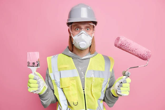 Studio shot of serious male construction worker uses repair tools for house remodeling