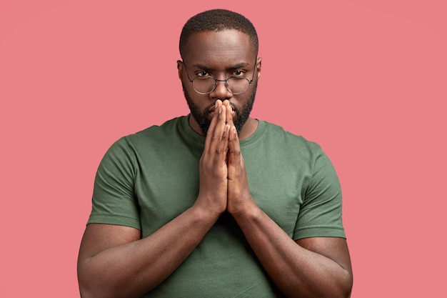 Studio shot of serious man keeps hands in praying gesture, worships for something