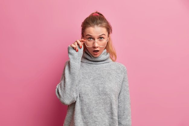 Studio shot of shocked european female model stares through transparent eyeglasses keeps mouth widely opened from astonishment