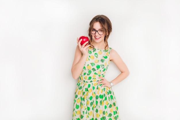 Studio shot di una ragazza bruna sorridente che sorride ampiamente. tiene una mela rossa nella mano destra