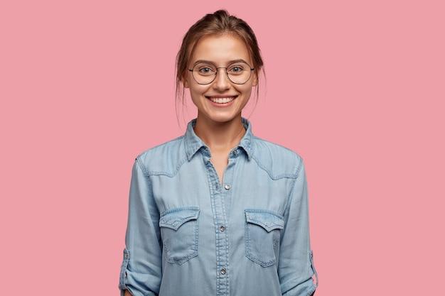 Studio shot di sorridere donna felice ha un aspetto accattivante