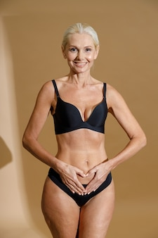 Studio shot of smiling mature blonde woman in black underwear holding hands on her belly forming a