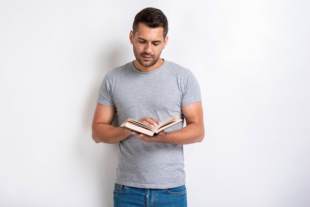 Studio shot of standing man holding a book and reading of it