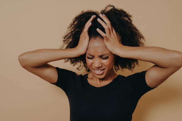 Studio shot of stressful and frustrated young african woman keeping head with both hands with closed eyes, displeased female suffering from headache or having problems at work. stress and depression