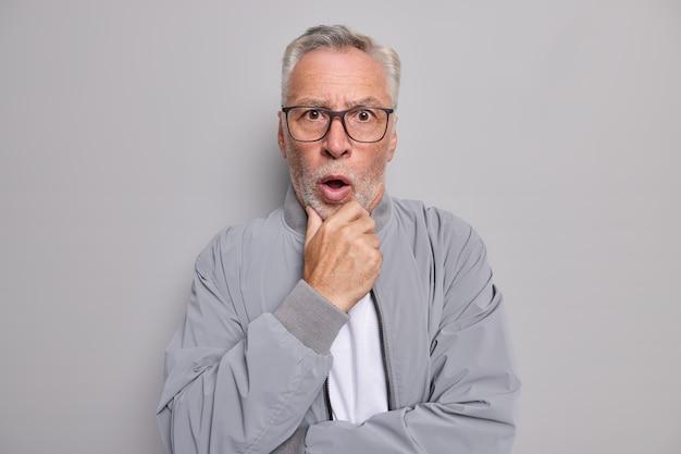 Studio shot of stunned bearded grey haired elderly man holds chin stands speechless