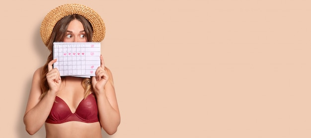 Studio shot of stunned european female holds period calendar, cons face, dressed in swimsuit, has surprised expression, stands on beige with copy space for your advertisement