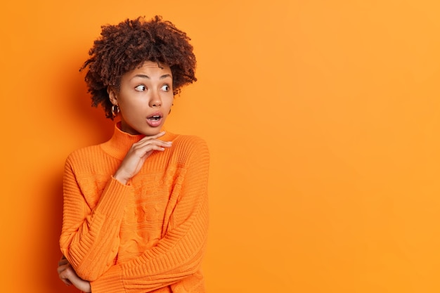 Studio shot of stupefied african american woman holds chin and stares aside