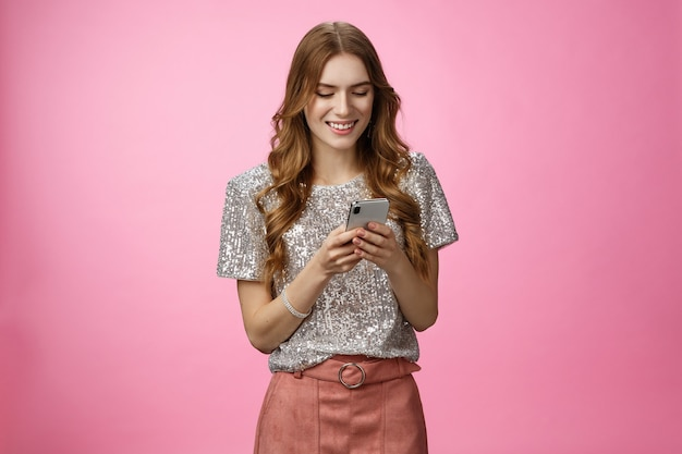 スタジオはスタイリッシュな魅力の若いヨーロッパのパーティーの女の子を待っているガールフレンドのテキストメッセージのスマートフォンの笑顔を撮影しました...