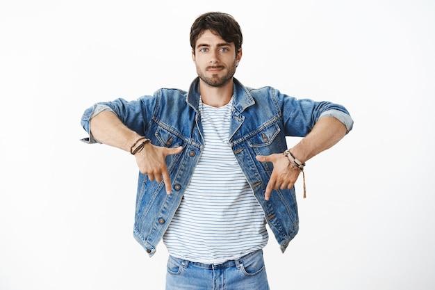 演播室射击了与胡子和蓝眼睛的时髦英俊的西班牙男性在举手和指向与显示好拷贝空间的好的被保障的微笑的时髦牛仔布夹克的时髦牛仔布夹克