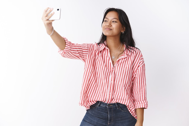 Studio shot of stylish young cute asian woman taking selfie to impress followers in internet with new trendy blouse extending hand with smartphone looking at mobile phone screen, photographing