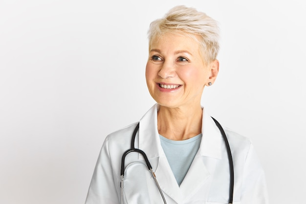 Studio shot of successful blonde middle aged female therapist posing isolated with broad happy smile wearing white medical gown and stethoscope around her neck