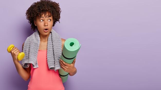 Studio shot di sorpreso donna afro fa esercizi con manubri, treni resistenza, utilizza tappetino fitness, vestito con abiti sportivi