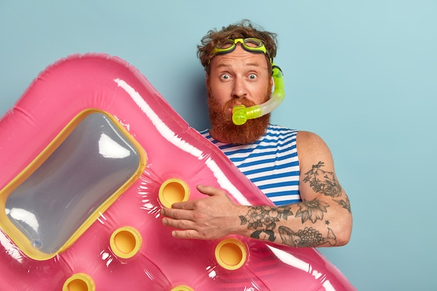 Studio shot of surprised bearded red man wears snorkel mask