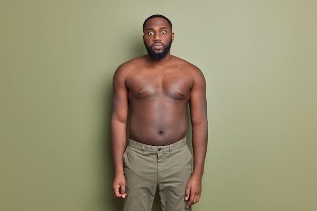 Studio shot of surprised dark skinned bearded man looks shocked and stunned keeps eyes widely opened