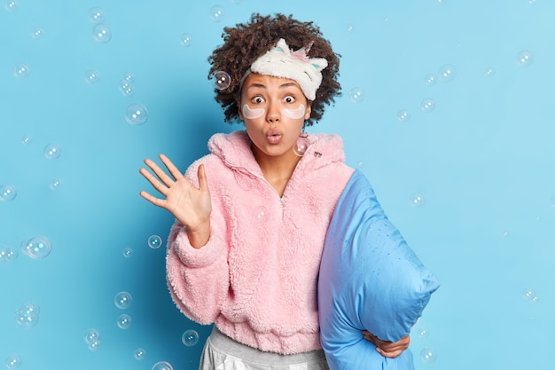 Studio shot of surprised dark skinned woman raises palm has wondered expression keeps lips rounded stares at camera holds pillow prepares for going to bed poses indoor soap bubbles flying in air