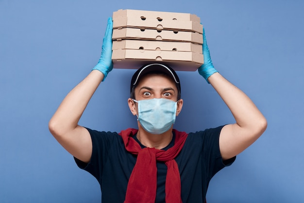 Studio shot of surprised delivery man dresses casual outfit, mask and latex gloves, holding stack of pizza's boxes above his head, has big eyes, looks shocked